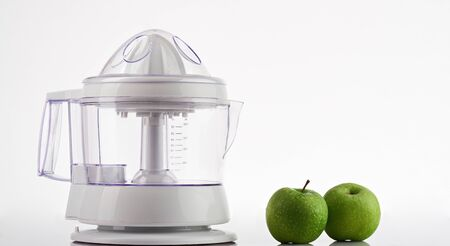 Two green apples with juicer isolated on wnite background