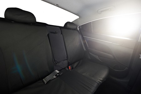 legroom: Sedan car interior of back black cloth seat with shining sun
