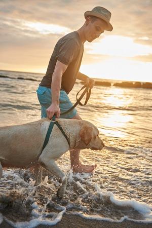 日没時にオーシャン ビーチに犬を連れて歩いて男