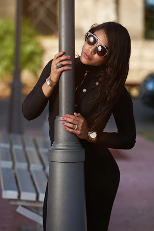 glamur: Portrait of woman standing behind light pole  in street day time