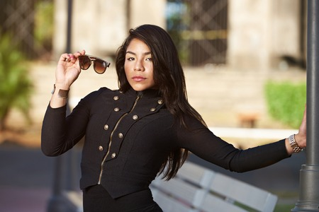 glamur: young hispanic woman hold sunglasses on day urban background