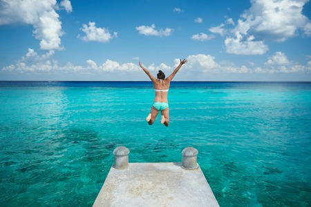 One woman jump in blue water from pier view from back on caribbean vacation