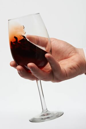 Checking red wine in glass with stem. Moving red wine in glass close up