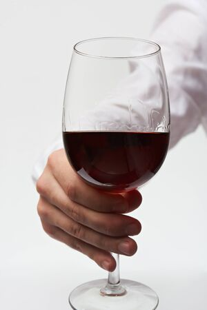 Hand holding wine glass via stem . Red wine glass in man hand isolated on white background. Test wine by sommelier