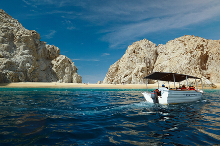 Boat moving to beach in Cabo San Lucas Mexico. Tourist going to beach on boat water taxi