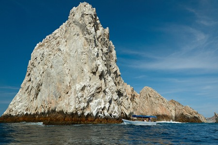 Boat close to big rock in Cabo San Lucas Mexico. Boat tour to huge rock at sea