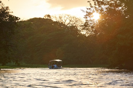 Small boat tour between islands in sunset time. Boat river tour