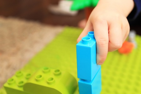 Child play with colorful constructor close-up. Kid build tower with cubics. Bright playing background. Stock Photo