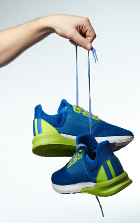 Hand holding colorful running shoes isolated on white background. Sport shoes hanging on laces