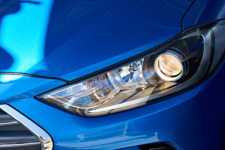 青い車の新しいヘッドライト。現代のスポーツ車のヘッドライトのクローズ アップ