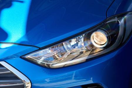 New headlight of blue car. Closeup of modern sport car head light Standard-Bild