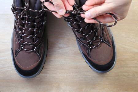 shoelace: Tourist tie shoelaces from above. Traveler tie shoelaces on trekking shoes on wooden floor. Stock Photo