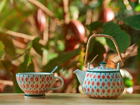 Tea cup on wooden table with blur bokeh plantation background