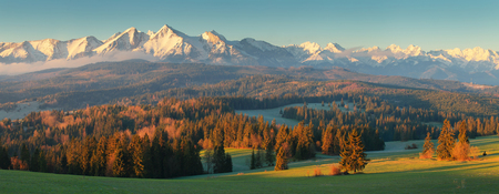 Summer morning in mountains. Green valley illuminated by rising sun. Snowy mountain peaks in morning sunlight. Beautiful panorama of Tatra mountains.