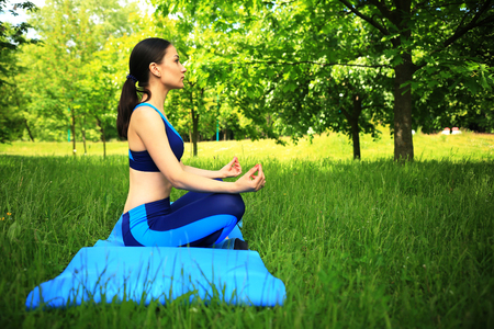 Fitness scene. Girl in lotos pose in park. Pretty girl doing yoga  outdoors.