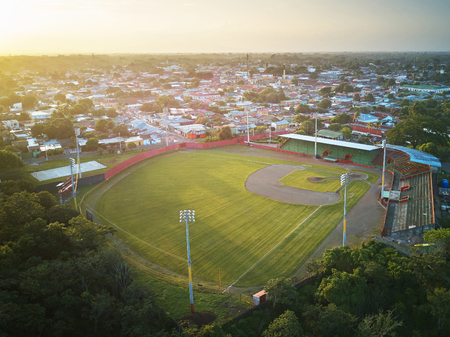 Green clean baseball field on small town landscape  drone view