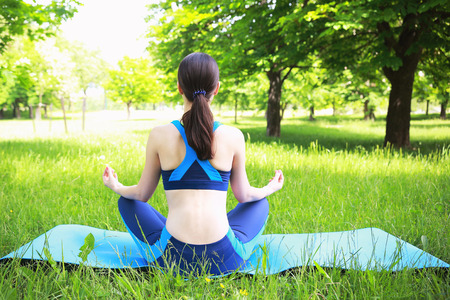 Girl does yoga exercise in park. Girl in lotos pose on green grass. Pretty girl doing yoga outdoors.