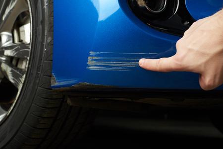 車塗料のスクラッチのクローズ アップ。指は青い車の傷を表示します。 写真素材