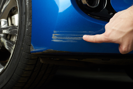 Car paint scratch close-up. Finger show scratch on blue car