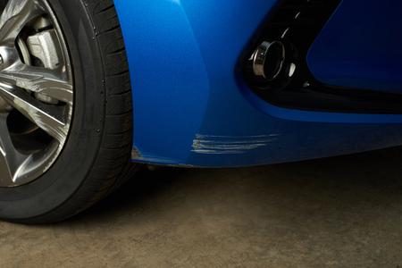 Scratched car bumper close-up. Scratch on blue paint. Damaged car detail Reklamní fotografie - 81603652