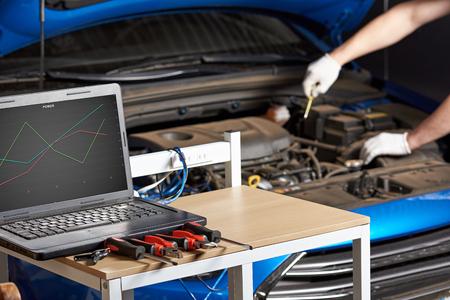 Equipment for electirc car testing with laptop. Diagnostic errors of modern car closeup.