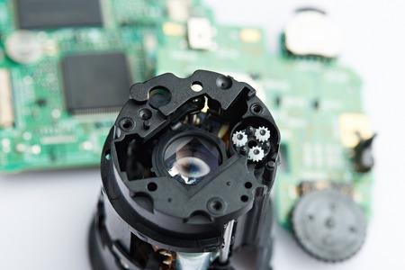 workroom: Dissassembled camera lens closeup. Repairing digital camera service
