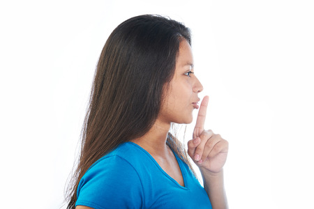 Young girl making shh gesture isolated on white background Standard-Bild