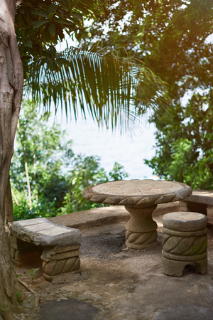 furniture design: Small patio with stone table and chairs on tropical background