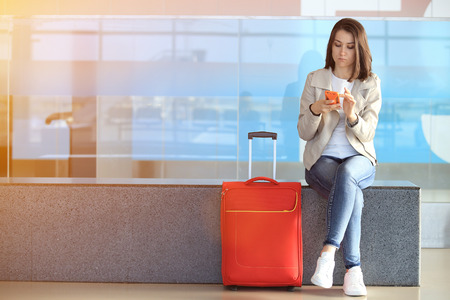 Girl with smartphone sitting near red suitcase in airport. Pretty girl wait for next flight.