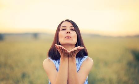 Girl blowing a kiss closeup. Woman on fresh air blowing a kiss.