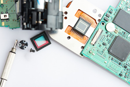 Dissassembled digital camera parts. Clean table with electronic DSLR camera parts Stock Photo