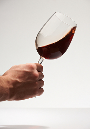 Red wine swirl in glass hand hold isolated on white background