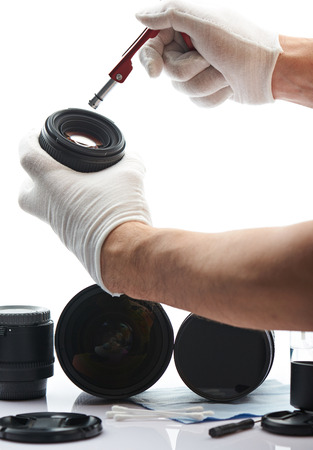 Maintenance of photo lens in white desk labaratory. Worker hands closeup in cleaning service