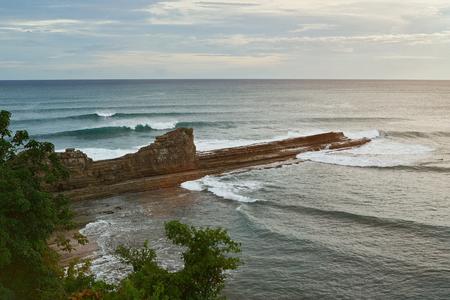amanecer: Ocean coastline in Nicaragua with big magnific rock on sunset time light Foto de archivo