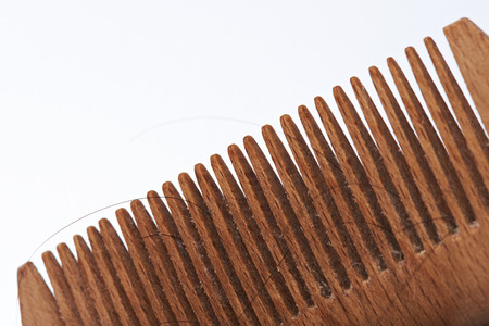 Close-up of wooden brush with lost dark human hair Stock Photo