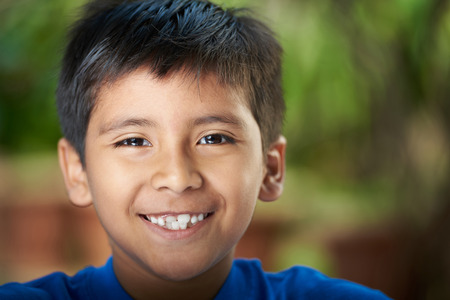 Close-up portrait of boy smiling with teeth. Hispanic boy headshot