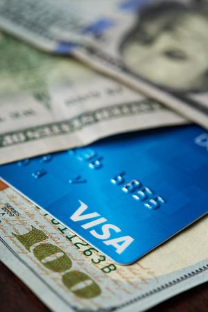 New york, USA - August 24, 2017: Blue credit visa card on hundred dollar bill background