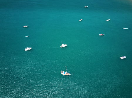 White boats in blue water  aerial drone view