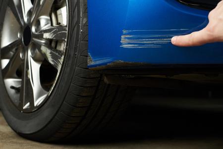 Peindre les rayures sur la voiture. Compagnie d'assurance vérifiant les dégâts de voiture