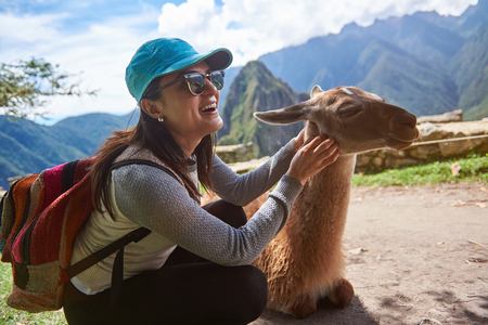 Smiling tourist woman with lama in Machu Picchu hiking travel. Happy girl in nature with alpaca