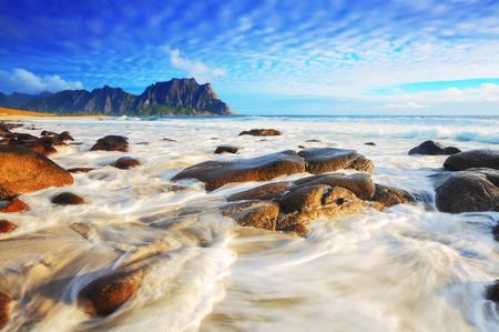 Sunny seascape. Tidal waves at the sunset. Vivid norwegian summer nature. Stock Photo