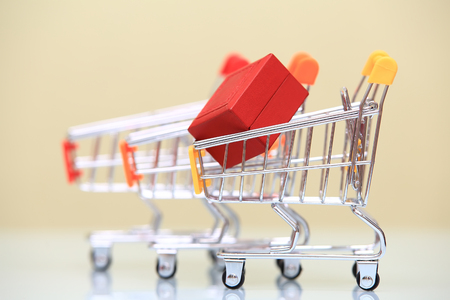 Gift shopping theme. Red gift box in shopping trolley close-up. Stock Photo