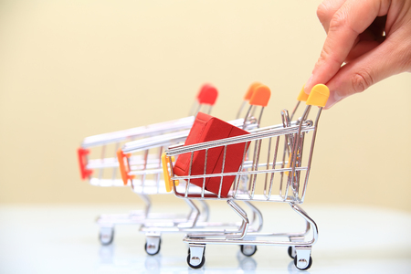 Christmas sale concept. Hand holds small shopping cart with red gift box close-up. Stock Photo