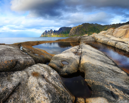 Seascape of Norway. Famous place on Tromso island in Norway. Teeth of Dragon beach. Big stones on seaside on a suny day.