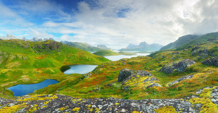 Sunny day in Norway. Green valleys in Norway mountains. Beautiful landscape of Lofoten islands with mountain lakes.