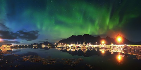 Northern lights over pier in Norway. Aurora borealis in night starry sky above fjord. Night scene with bright northern lights. Stock fotó