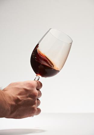 Hand het schudden glas met rode die wijn op witte achtergrond wordt geïsoleerd