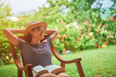 Happy comfortable young woman in terrace on sunny summer day background