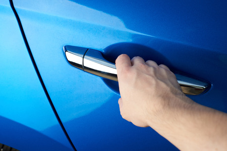 Opening car door close-up. Hand hold car door handle Stock Photo