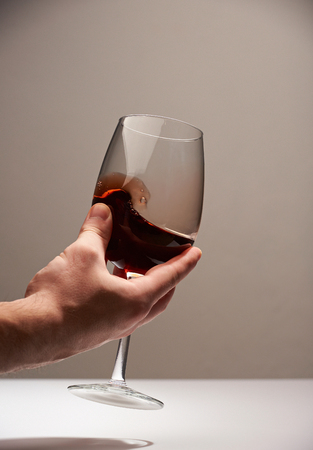 Hand hold elegant glass with red wine into it